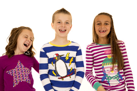 Adorable children laughing wearing colorful Christmas pajamas