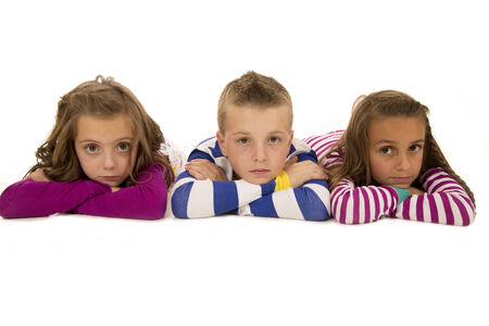 laying forward: Children laying down wearing pajamas looking forward