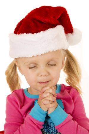 Cute young girl praying wearing santa hat photo
