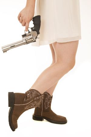 waist down: Cowgirl dress from waist down holding revolver