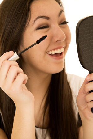 Cute ethnic teen applying her mascara laughing photo