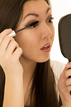 Beautiful teen model applying mascara holding mirror photo