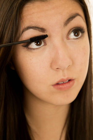 Asian American beauty teen girl applying mascara photo