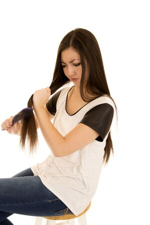 Cute teen girl frustrated brushing her hair photo