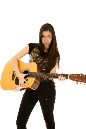 younger: Younger female model playing guitar serious expression