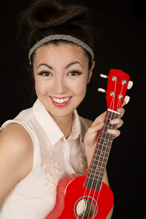 Beautiful teen girl holding red ukulele smiling photo