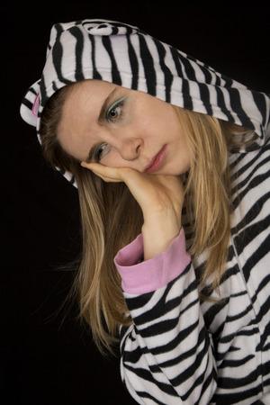 striped pajamas: Sad young woman wearing striped cat pajamas Stock Photo