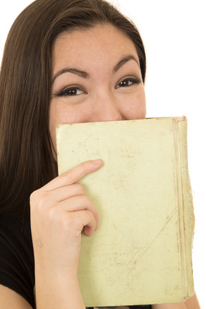 covering the face: Young student laughing behind book covering face