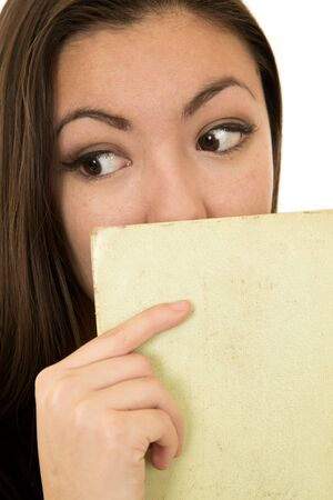 sidewards: Woman glancing sidewards holding book to face