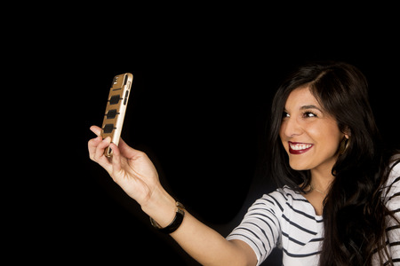 dark haired: Happy beautiful dark haired female taking selfie picture smiling Stock Photo