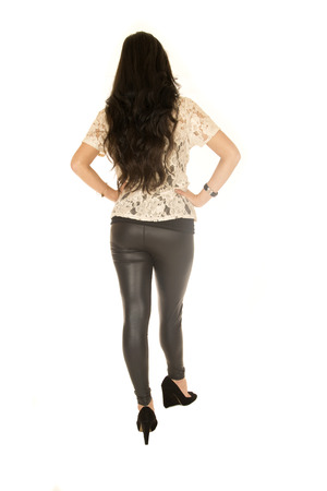 long pants: Long haired brunette wearing high heels and black leather tight pants rear view Stock Photo