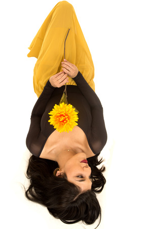 woman laying down: Peaceful woman laying down holding yellow flower Stock Photo