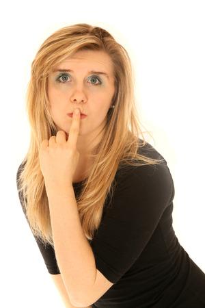 finger on lips: blond blue eyed female finger to lips Stock Photo
