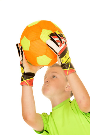 goalie: Intense expression boy soccer goalie catching ball Stock Photo