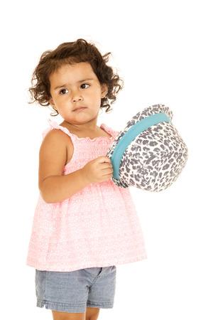glancing: Hispanic toddler girl holding hat glancing sidewards Stock Photo