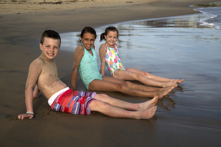 Preteen children sitting on beach in water