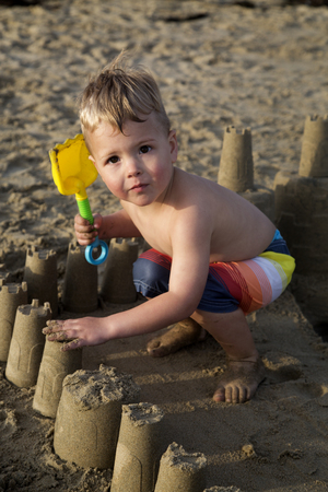 brown  eyed: Brown eyed blond boy playing in sandcastle