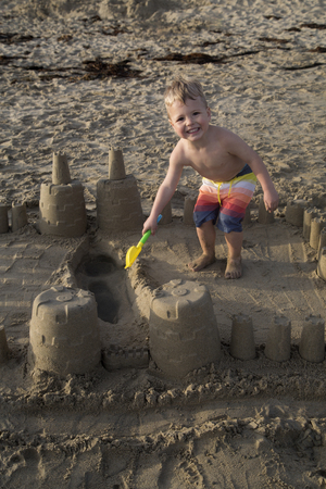 Young blond boy playing in sand castle