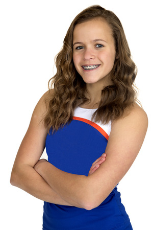 Teenage cheerleader blue uniform arms folded smiling Stock Photo