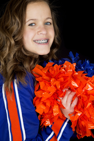 Portrait teen cheerleader holding pom poms smiling