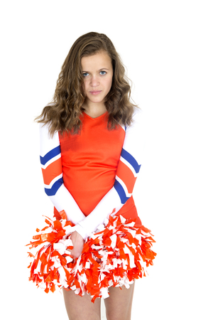 Beautiful teen cheerleader standing holding orange pom-poms