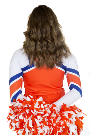 Back of girl cheerleader holding orange pom-poms