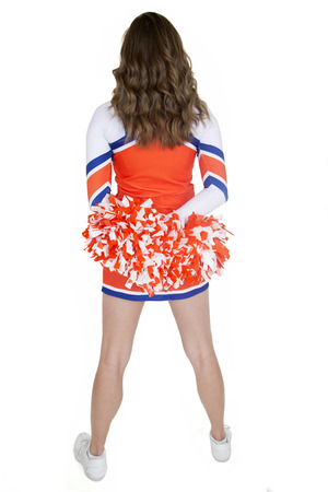 Back of teen cheerleader standing orange pom-poms