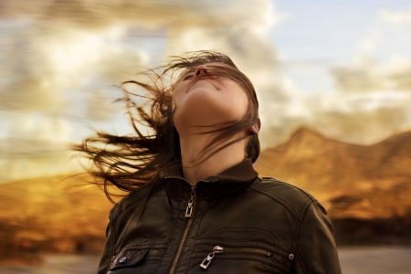 Woman with hair blowing in the wind breathing deeply and looking up wearing a leather jacket with a blurred nature background