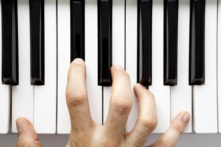 A hand playing the piano from a high angle view photo