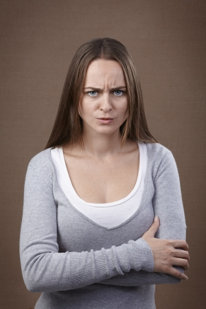 exacting: Young adult woman looking at camera displeased and angry Stock Photo