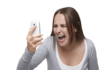 exacting: Woman looking at her mobile phone and shouting it
