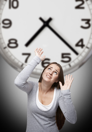 oppress: Woman looking up and trying to stop a big clock above her with a gray background