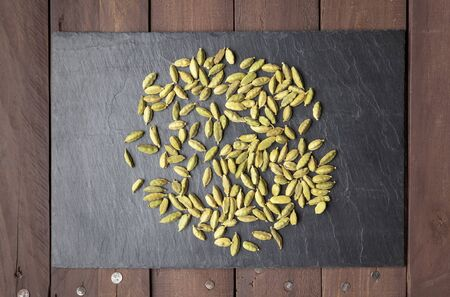 scatter: Cardamom seeds scattered on a square shaped slate plate on a brown wooden table.