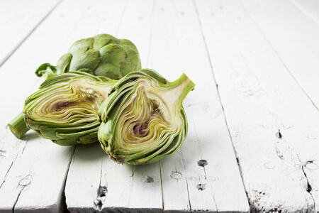 close up food: Two artichokes, one of them cut in half, on a wooden white table, with copy space