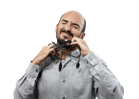 take out: Young adult man, with a dramatic expression, tries to take out some USB cables of around his neck. Stock Photo