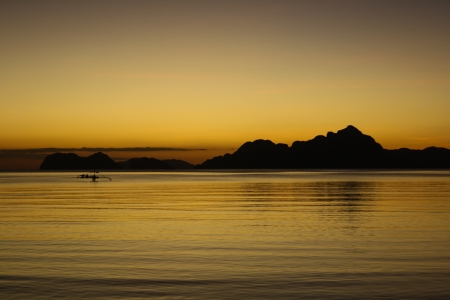 Sunset from El Nido beach with a silhoutte of a bangka boat. Palawan, Philippines photo