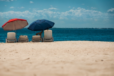 mujeres: A person relaxing under an umbrella on a white sand beach