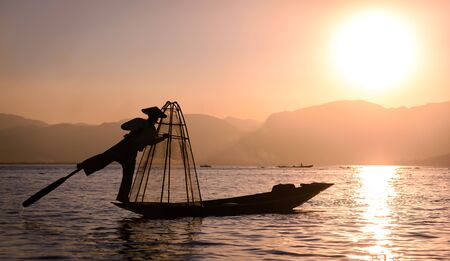 inle: Silhoueete of a fisherman on Inle Lake, Burma