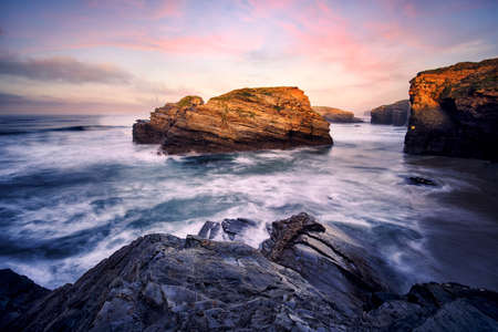 Sea lashes the rocky shoreline at sunset
