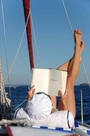 Young beautiful woman is relaxing and sunbathing while reading a book on a sailboat in the open adriatic sea. Book can be used as copy space for small alterations. photo
