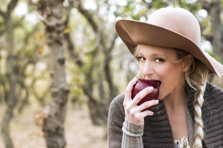 Healthy young woman with hat on her head eating red apple in the wood  Stock Photo - 12858968