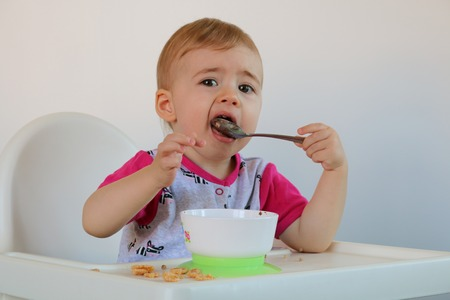 eat smeared baby: Little smiling baby sits at highchair and eats porridge on plate. white background Stock Photo
