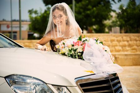 love very: bride with bouquet near the car on a hot summer day Stock Photo