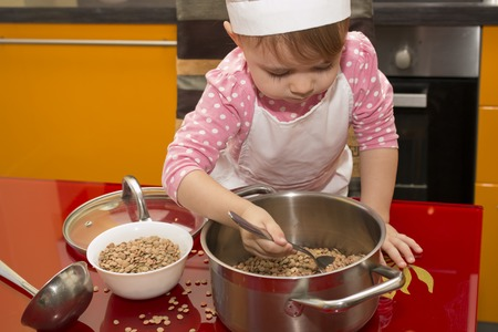 Prodigy: The little girl in a suit of the cook sculpts dough. Baby make dinner in chef suit