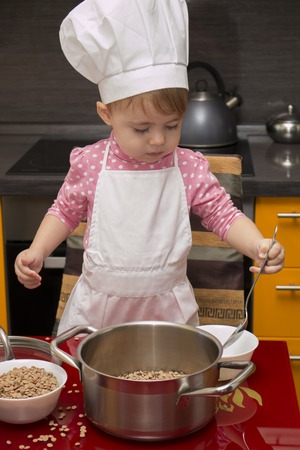 Prodigy: little cute girl playing in the kitchen with a ladle and saucepan