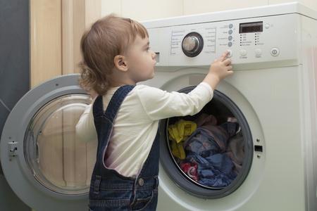 little girl starts washing machine in the bathroom Фото со стока