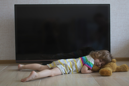 Conceptual portrait little girl is sleeping on the floor on the background of a black TV screen