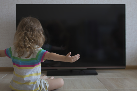 Conceptual portrait. Little girl girl spread her arms out to the sides sits on the background of a black TV screen