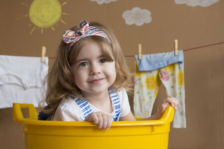 little girl is sitting in a yellow bath Stock Photo