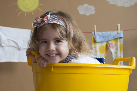 cute little girl smiles and sits in a yellow bath Stock Photo